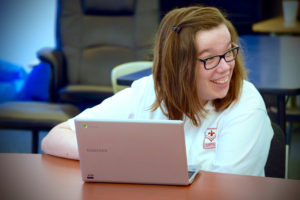Emily using assistive technology at the Academy